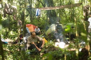 Phillip Jordaan, Professor Julian Bayliss, Bartholomew Ofelio and Ofelio Cavaliao try to dry out with a fire and take time to clean and fix feet after five days deep the in the forest