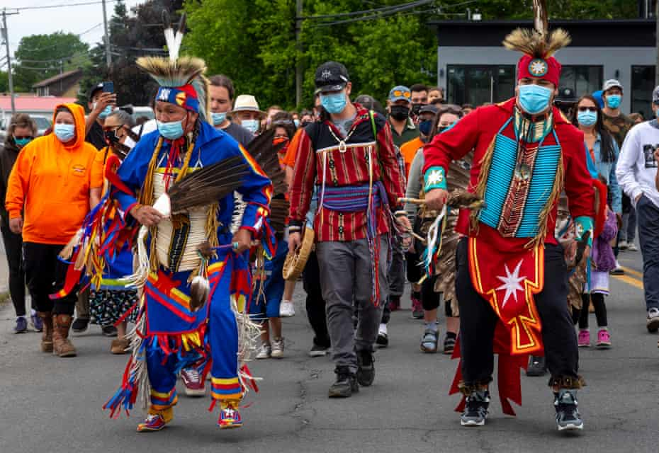 Members of the community of the Kahnawake Mohawk Territory, Quebec, march through the town on 30 May to commemorate the news that a mass grave of 215 Indigenous children was found at the Kamloops residential school.
