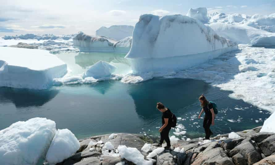 Visitors walk among free-floating ice jammed into the Ilulissat Icefjord during unseasonably warm weather on July 30, 2019 near Ilulissat, Greenland.