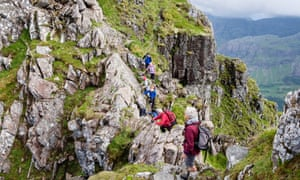 Hikers scrambling on steep rocky pinnacles of Aonach Eagach ridge