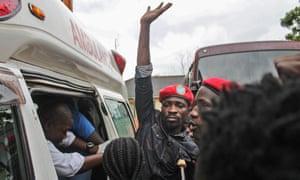 Robert Kyagulanyi Ssentamu, AKA Bobi Wine, waves to supporters before climbing into an ambulance after being released on bail in Gulu, northern Uganda.