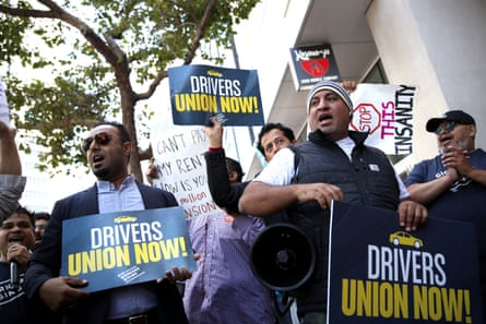 Rideshare drivers wave flags and hold signs during a protest outside Uber headquarters last year.