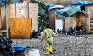A child walks at a camp for migrants and refugees in Grande-Synthe, northern France, on November 18, 2016.