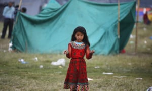 A girl stands outside her makeshift shelter in an open space in the early hours