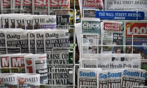 Newspapers are displayed on a stand outside a newsagent in London