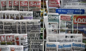 Newspapers are displayed on a stand outside a newsagent in London, England.