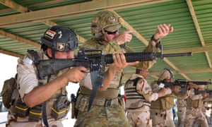 An Australian army trainer demonstrates the correct standing position to an Iraqi army soldier during marksmanship training at the Taji Military Complex in Iraq.