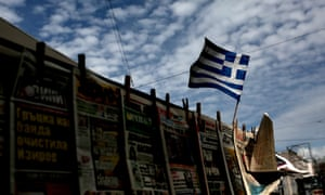 The Greek national flag flutters over of a kiosk in Athens on March 1, 2015.