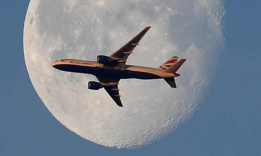 A British Airways passenger plane flies in front of the moon