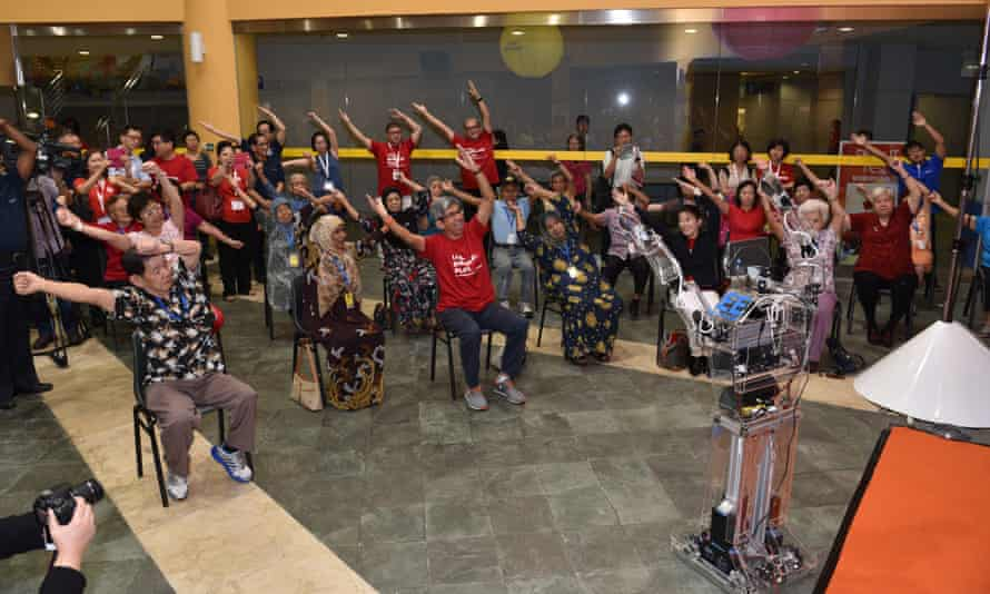 Yaacob Ibrahim (centre front) works out with Robocoach in Singapore.