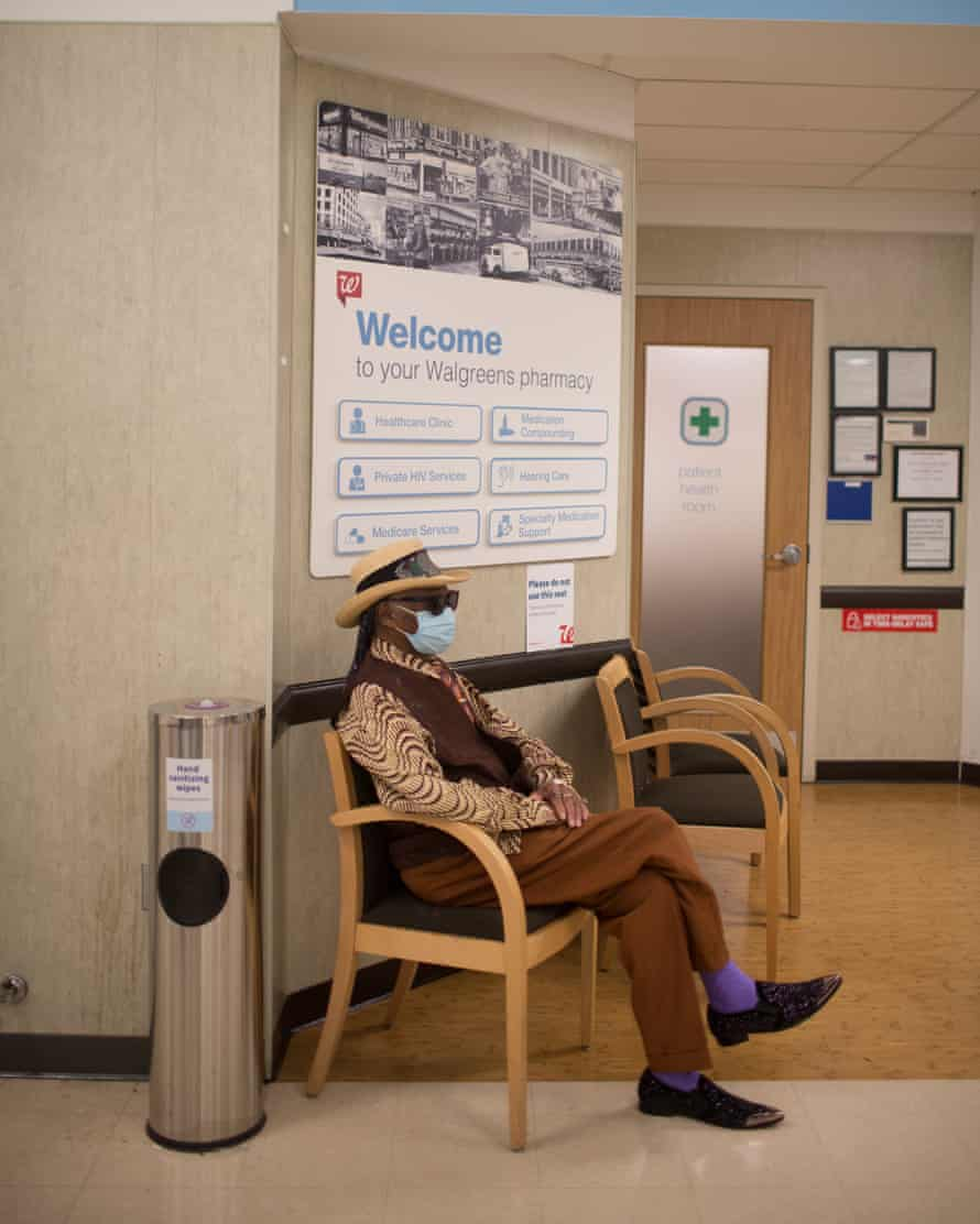 The bluesman at a local Walgreens waits to get a Covid vaccine. His outfit – a pointed hat, shades, and a sharp brown waistcoat – is again at odds with the sterile surroundings.