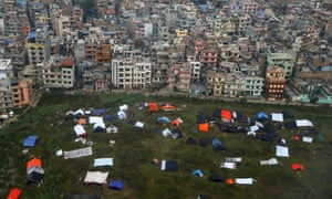 Earthquake survivors sleep in provisional tents and under plastic sheets near the airport