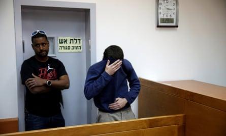 Michael Kadar hiding his face in court in Rishon Lezion, Israel