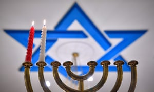 Two candles of a Hanukkah candle holder burn