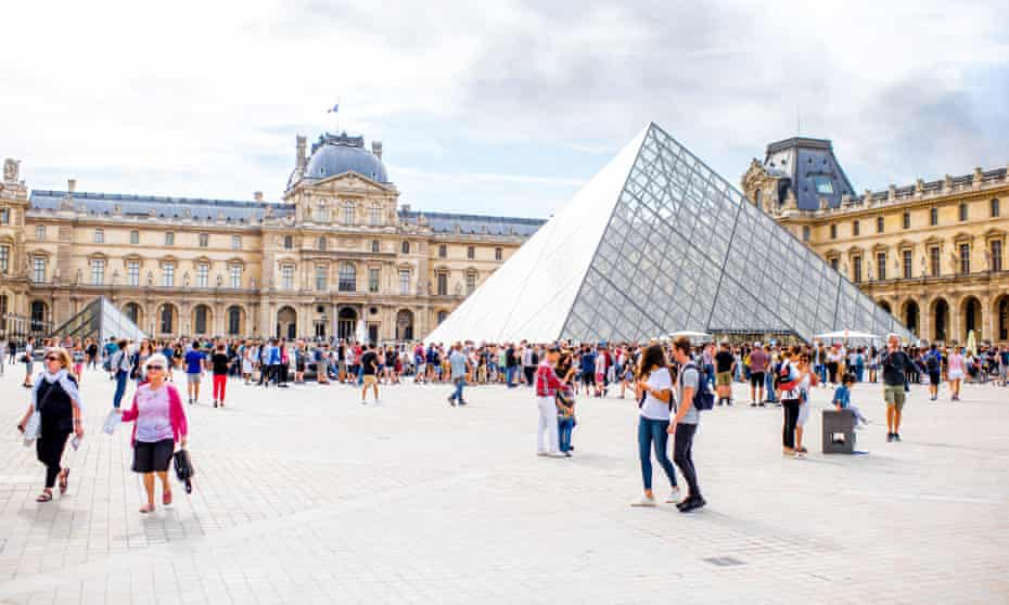 View on the Louvre museum square, Paris full of people during the cloudy weather.