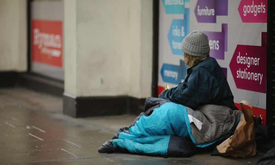 Homeless person sits in a shop doorway