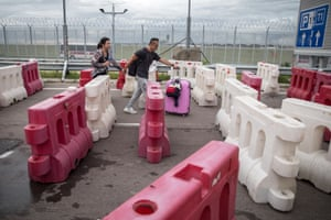 Travelers wheel their luggage through a barricade built by protesters on the road leading to Hong Kong International Airport, September 1, 2019 .