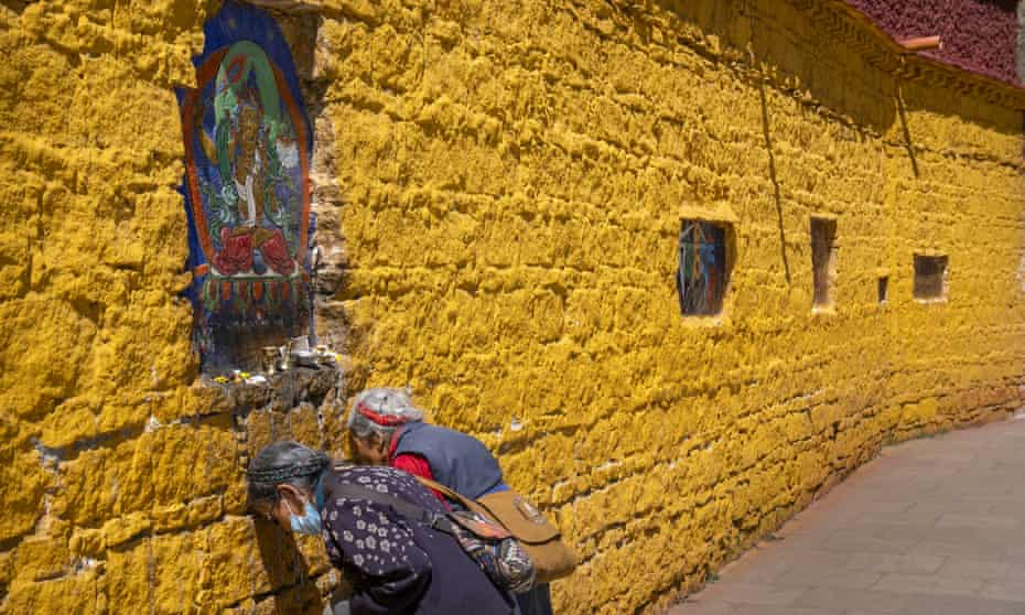 Members of the Tibetan Buddhist faithful pay their respects at a holy site