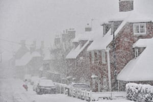 A man stands in the falling snow holding a sledge in the village of Brenchley