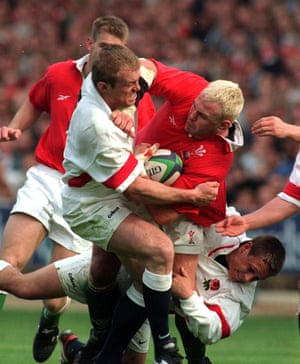 Wales' Scott Quinnell is tackled by England's Tim Rodber (left) and Johnny Wilkinson.