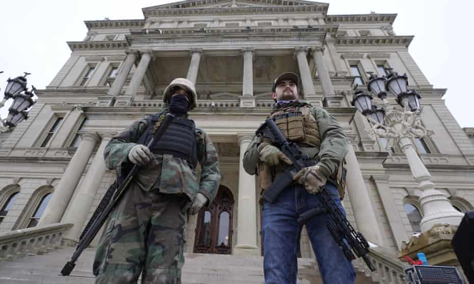 Armed men stand on the steps at the Michigan state capitol after a rally in support of President Donald Trump in Lansing on 6 January 2001.