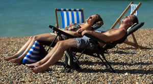 A couple relax on the beach in Brighton, East Sussex