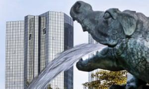 A víz egy kis sárkány-szoborból kifolyik a szökőkúton, a Deutsche Bank székhelyével, Frankfurtban, Németországban.