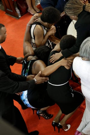 Ushers come to the assistance of a woman who collapses as she prays
