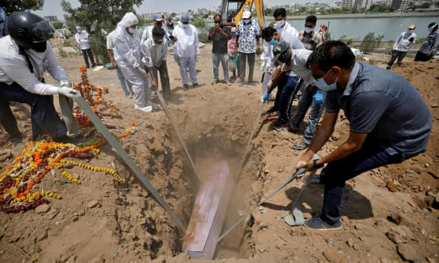 People lower the body of 65-year-old Arnold Samuel Christian, who died from coronavirus into a grave at a cemetery in Ahmedabad
