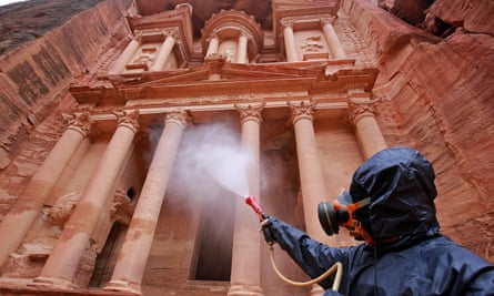A man in full PPE using a long lance to spray the famous rock facade of the ancient city of Petra