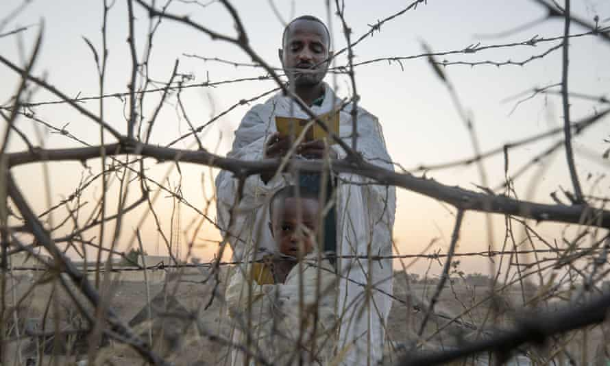 An Orthodox Christian refugee who fled the conflict in Tigray reads prayers with his son at the Hamdeyat transition centre near the Sudan-Ethiopia border