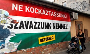 A woman walks in front of a Hungarian goverment referendum poster