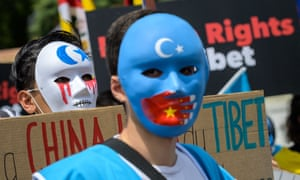 Tibetan and Uyghur activists wear masks during a protest against the Beijing 2022 Winter Olympics.
