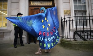A pro-EU activist wearing a cape decorated with an EU flag design joins a rally organised by civil rights group New Europeans outside Europe House.