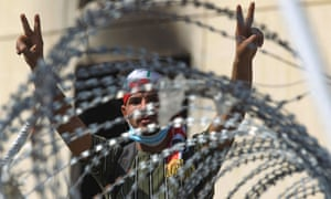 An Iraqi protester flashes the victory sign from behind barbed wire near Baghdad's Al-Jumhuriyah bridge.