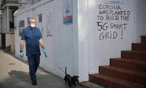 A man wearing a protective mask and gloves walks his dog past graffiti that reads 'Corona was planted to build the 5G smart grid!'