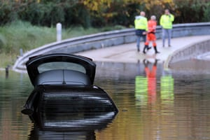 Mandelieu-la-Napoule, France, Rescuers walk by a car partially submerged in the water on a flooded road, following fresh torrential rains over the French Riviera