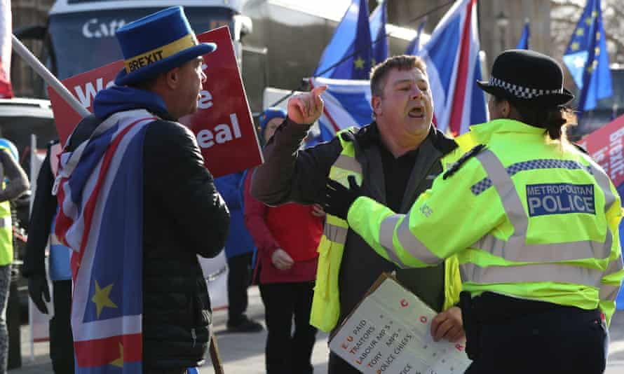 A leave supporter is spoken to by a police officer as he argues with a remain supporter outside parliament