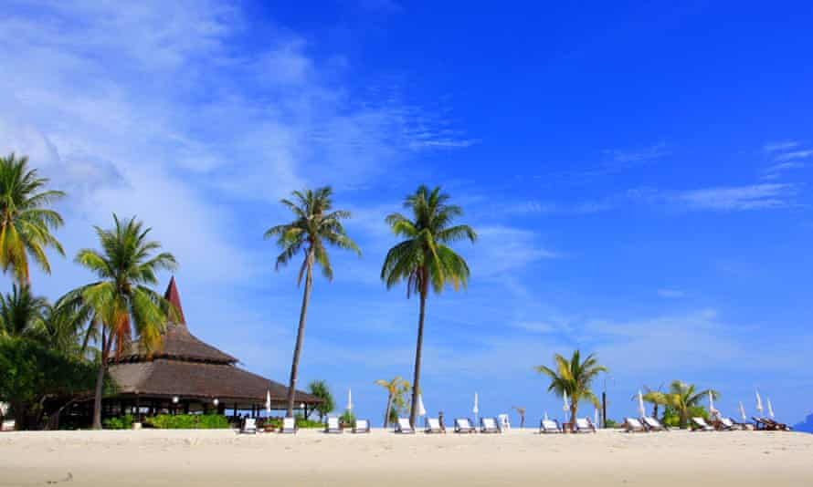Sivalai Beach Resort on a blue-sky day with empty sun-loungers set on the beach. Koh Muk, Thailand.