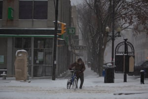 A man struggles in the snow with his bicycle as the first big winter storms hit the region, Saskatoon, Canada