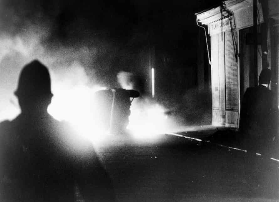 Police officers watching a burning car on Railton Road during the Brixton riots