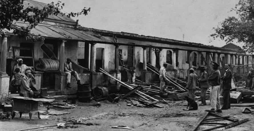 A family watches as demolition workers tear down a row of neighbourhood homes in Sophiatown, 1955.
