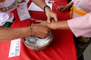A Balinese woman marks her finger with ink after voting.
