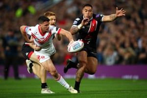 Lachlan Coote of St Helens is tackled by Kris Welham and Ken Sio of Salford Red Devils.