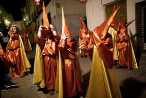 Children from the Santisimo Cristo de la Misericordia (Holy Christ of Mercy) brotherhood remove their hoods after a procession in Caravaca de la Cruz, Murcia