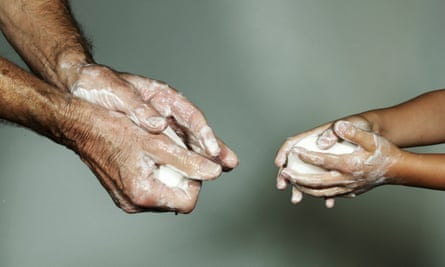 Man and young child washing hands with soap