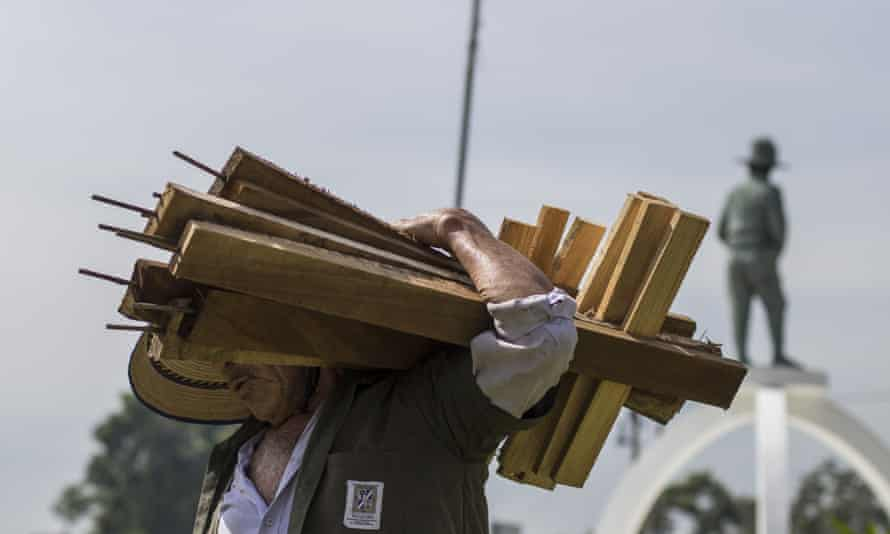 A city employee removes wooden crosses that were placed in a plaza by organizations protesting against the government inaction over the alarming murder rate in San Salvador, El Salvador.