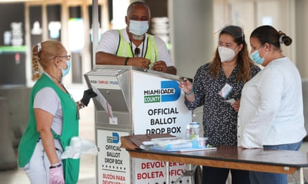 Poll workers help a voter put their mail-in ballot in an official Miami-Dade county ballot drop box on Tuesday in Miami, Florida.