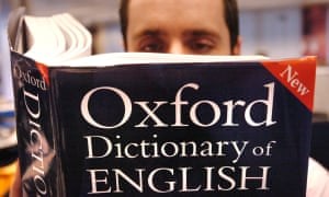 A man (posed by model) reading a copy of the Oxford Dictionary of English