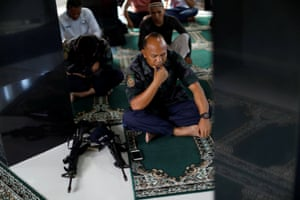A police officer performs Eid al-Fitr prayers at a mosque inside city hall in Marawi City, Philippines